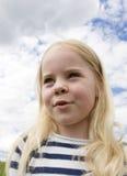 Bambina contro il cielo nuvoloso Immagine Stock