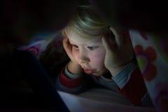 Bambina in coperta che fissa allo schermo d'ardore della compressa Fotografia Stock