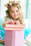 Bambina coperta di corona e di libri fotografia stock