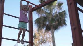 Bambina coraggiosa che appende sulle scale nel campo da giuoco video d archivio