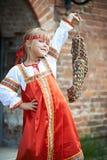 Bambina in costumi nazionali con rafia Immagine Stock