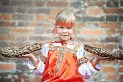 Bambina in costumi nazionali con rafia Fotografia Stock