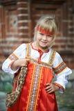 Bambina in costumi nazionali in villaggio russo Fotografia Stock