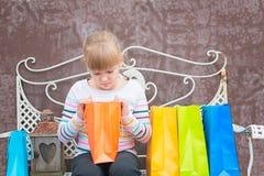 Bambina curiosa che guarda nella borsa Fotografia Stock