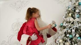 Bambina d'aiuto di Santa Claus per appendere le bagattelle sopra l'albero di Natale stock footage