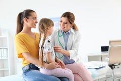 Bambina d'esame del medico dei bambini vicino al genitore fotografie stock