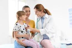 Bambina d'esame del medico dei bambini vicino al genitore fotografia stock libera da diritti