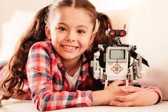 Bambina d'orientamento che abbraccia il suo nuovo giocattolo del robot immagine stock libera da diritti