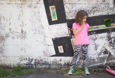 Bambina davanti alla parete dei graffiti immagini stock