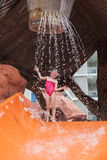 Bambina davanti alla posa dell'acquascivolo del parco dell'acqua Fotografia Stock Libera da Diritti