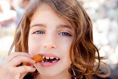 Bambina degli occhi azzurri che mangia i crullers fritti fotografia stock