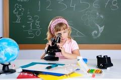 Bambina dei bambini al banco con il microscopio Fotografia Stock Libera da Diritti