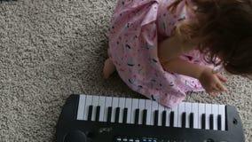 Bambina del bambino che gioca su un piano del giocattolo Video completo di HD video d archivio