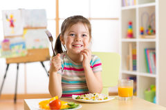 Bambina del bambino con l'alimento sano pronto da mangiare della forcella fotografia stock libera da diritti
