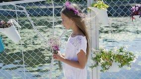 Bambina delicata con i fiori a disposizione che sorride e che esamina macchina fotografica sulla barra di baia archivi video