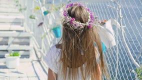 Bambina delicata con i fiori a disposizione che sorride e che esamina macchina fotografica sulla barra di baia stock footage