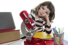 Bambina dell'allievo con il microscopio ed il computer portatile Fotografia Stock