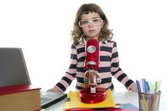 Bambina dell'allievo con il microscopio ed il computer portatile Immagine Stock