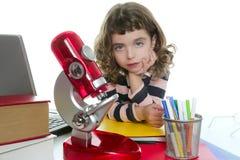 Bambina dell'allievo con il microscopio ed il computer portatile Fotografia Stock Libera da Diritti