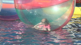 Bambina dentro una grande palla gonfiabile in acqua stock footage