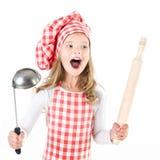 Bambina di grido in cappello del cuoco unico con la siviera ed il matterello Immagini Stock Libere da Diritti