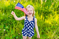 Bambina di risata con la bandiera americana lunga della tenuta dei capelli biondi Immagini Stock
