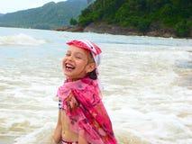 Bambina di risata sulla spiaggia immagine stock