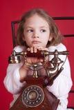 Bambina di Thougtful con il vecchio telefono fotografia stock
