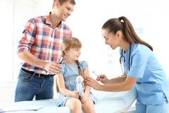 Bambina di vaccinazione del medico dei bambini vicino al genitore fotografia stock libera da diritti