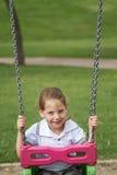 Bambina divertendosi su un'oscillazione in un parco verde Immagini Stock Libere da Diritti