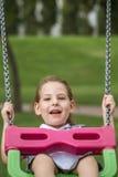 Bambina divertendosi su un'oscillazione in un parco verde Fotografia Stock