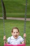 Bambina divertendosi su un'oscillazione in un parco verde Fotografie Stock Libere da Diritti