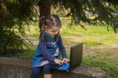 Bambina divertente che impara con il pc della compressa nel parco Immagine Stock