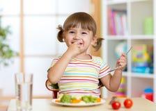 Bambina divertente che mangia alimento sano nell'asilo fotografia stock libera da diritti