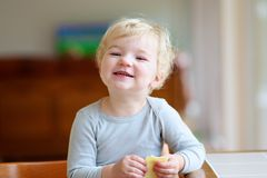 Bambina divertente che mangia panino a casa Fotografie Stock
