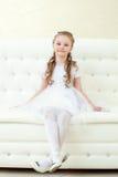 Bambina divertente che posa seduta sullo strato bianco immagini stock libere da diritti