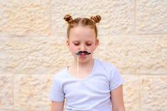 Bambina divertente con le maschere di carta di carnevale dei baffi divertendosi sul fondo bianco della parete fotografia stock libera da diritti