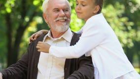 Bambina dolce che abbraccia nonno handicappato che si siede in sedia a rotelle, famiglia video d archivio