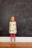 Bambina dolce che pensa davanti alla lavagna Fotografia Stock Libera da Diritti