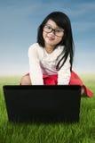 Bambina dolce che per mezzo del computer portatile al campo Fotografia Stock Libera da Diritti