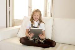 Bambina dolce che si siede sullo strato domestico del sofà facendo uso di Internet app sul cuscinetto digitale della compressa Immagine Stock Libera da Diritti