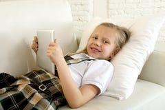 Bambina dolce che si trova sullo strato domestico del sofà facendo uso di Internet app sul cuscinetto digitale della compressa Immagini Stock