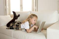 Bambina dolce che si trova sullo strato domestico del sofà facendo uso di Internet app sul cuscinetto digitale della compressa Fotografie Stock Libere da Diritti