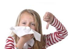 Bambina dolce e sveglia dei capelli biondi che soffia il suo naso con il tessuto di carta avendo il raffreddore sentirsi male Immagini Stock