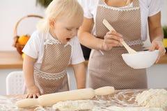 Bambina e la sua mamma bionda in grembiuli beige che giocano e che ridono mentre impastando la pasta nella cucina Homemad Immagine Stock Libera da Diritti
