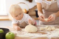 Bambina e la sua mamma bionda in grembiuli beige che giocano e che ridono mentre impastando la pasta nella cucina Homemad Immagini Stock Libere da Diritti