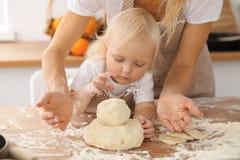Bambina e la sua mamma bionda in grembiuli beige che giocano e che ridono mentre impastando la pasta nella cucina Homemad Fotografie Stock Libere da Diritti