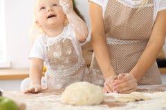 Bambina e la sua mamma bionda in grembiuli beige che giocano e che ridono mentre impastando la pasta nella cucina Homemad Immagini Stock