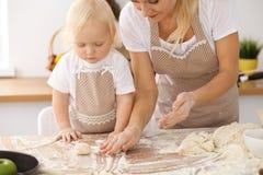 Bambina e la sua mamma bionda in grembiuli beige che giocano e che ridono mentre impastando la pasta nella cucina Homemad Immagine Stock