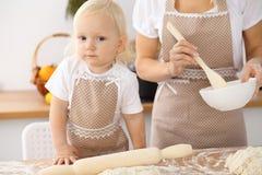 Bambina e la sua mamma bionda in grembiuli beige che giocano e che ridono mentre impastando la pasta nella cucina Homemad Fotografie Stock
